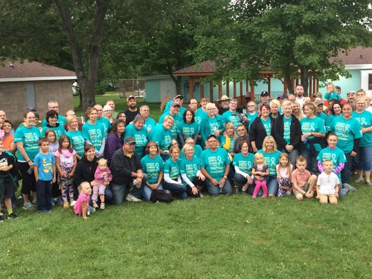 A large group of walkers pose after walking at A Walk Together For Suicide Awareness on Friday at Medford City Park in Medford.