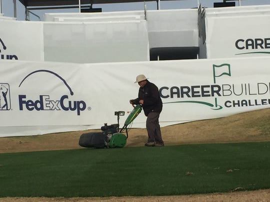 A maintenance worker mows the 17th tee of the Stadium Course at PGA West in front of the Club 17 hospitality tent at this year's CareerBuilder Challenge.