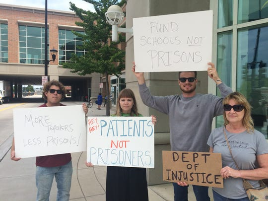 Protesters hold signs outside the KI Convention Center in Green Bay, where Attorney General Jeff Sessions spoke Tuesday about combating opioid abuse.