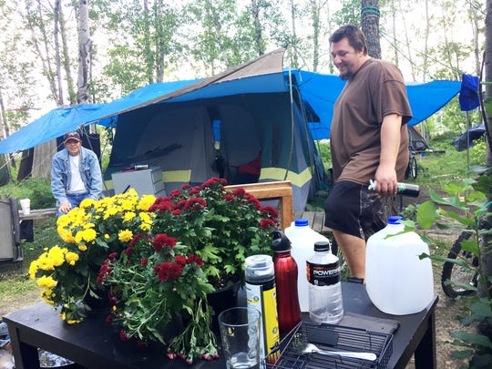Nick Walls, 32, who is homeless, speaks at his campsite in Burlington's South End. Walter Putnam, 55, at left, is a former resident of the camp. Photographed Aug. 23, 2017.