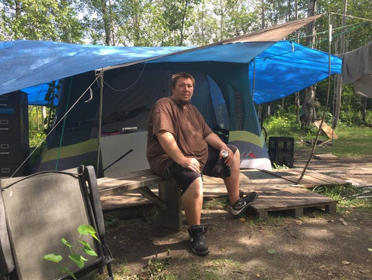 Nick Walls, 32, who is homeless, sits at his campsite