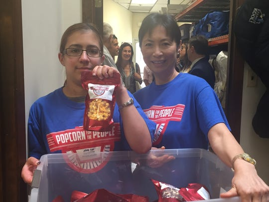 An employee of Popcorn For The People, Gabby Monard, 22, of Spotswood, and Marisa Shah, of Edison, a Fulfillment Center worker,  show off some flavors of the popcorn they sell. Popcorn For The People officially opened their new headquarters on Harts Lane in East Brunswick on Wednesday.