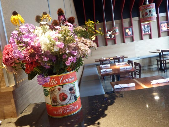 A tomato can holds flowers inside Maggie's Farm Wood-Fired Pizza in University Heights on Aug. 31, 2017.
