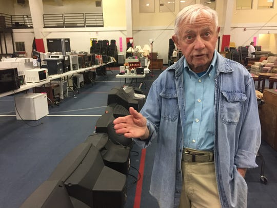 """John Groppe, a professor emeritus of English at Saint Joseph's College, looks through the rows of desks, computers and band instruments in the Hanson Recreation Center on Wednesday. Groppe said the ongoing liquidation is """"one more punch to the gut"""" reminding him and the community that the college closed at the end of the 2016-17 school year."""