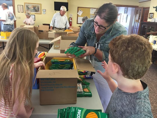 Megan Ames, center, helps gather school supplies with Victoria Arvidson, 11, and Christopher Ames, 8 at Naomi Makemie Presbyterian Church in Onancock, Virginia on Wednesday, Aug. 30, 2017. The Eastern Shore of Virginia's four Presbyterian churches donate school supplies for needy students to seven area schools and the Eastern Shore Coalition Against Domestic Violence.
