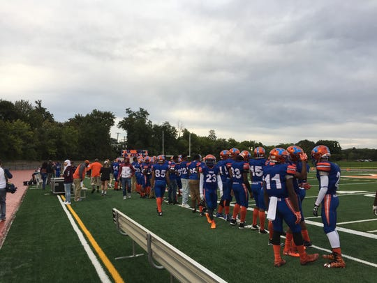 York High football players stand on the sidelines before