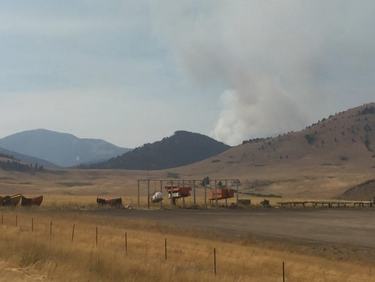A cloud of smoke billows up from the Alice Creek Fire