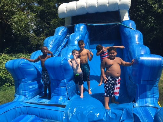 Dominik Glorioso (right) and his friends play on a water slide at his birthday party