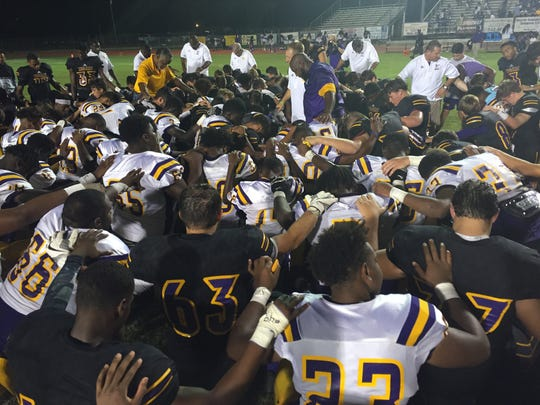 Benton head coach Reynolds Moore (center) and Wossman head coach Dean Smith bring their teams together for a prayer following Friday's game at Benton.
