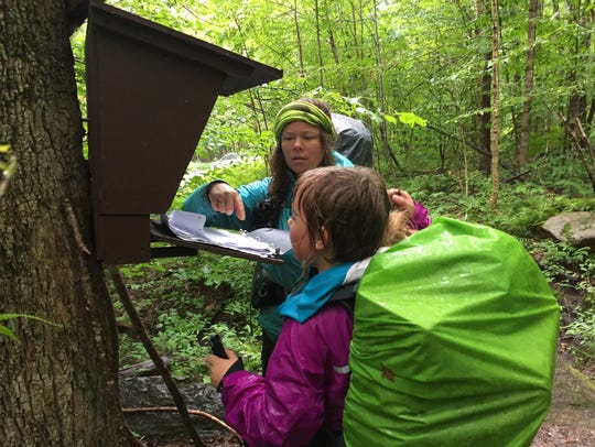 Yarrow Upton and her daughter, Zella, sign a trail