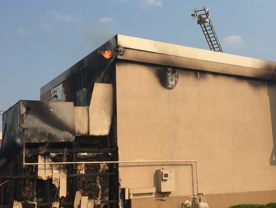 Flames emerge from an attic area at the rear of the
