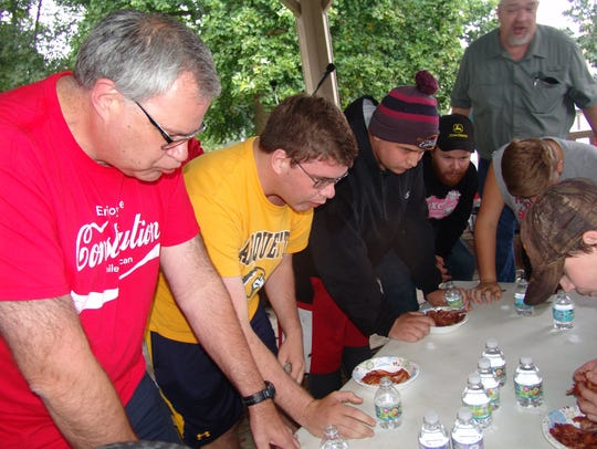 Participants register and weigh the bacon before the