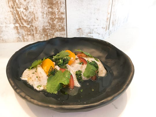 A crudo of sole served with cilantro and colorful slices of heirloom tomatoes is seen on the dining counter at Moody Rooster, which opened Aug. 29 in Thousand Oaks.