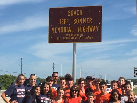 Members of the Estero cross country and track teams gather underneath the sign for the newly dedicated Jeff Sommer Memorial Highway in Estero. Sommer, the longtime athletic director and coach at Estero, died in 2015 while coaching his runners at the state track meet.