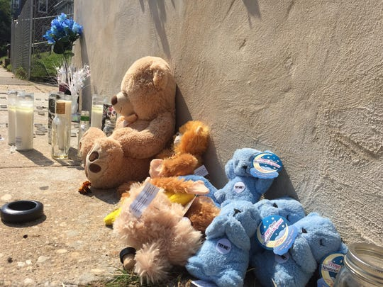 Burned-out candles, flowers and stuffed toys lined the concrete garden on West 26th Street where 19-year-old Barry White was killed this weekend.