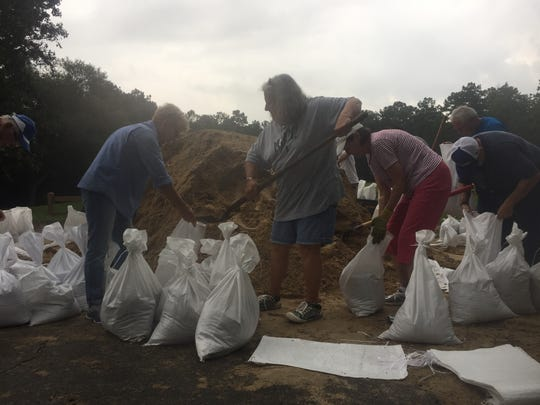 People fill sandbags at Tekesta Park Wednesday morning in preparation for Hurricane Irma.