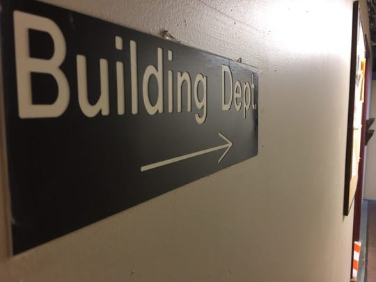 A sign directs patrons to the building department in