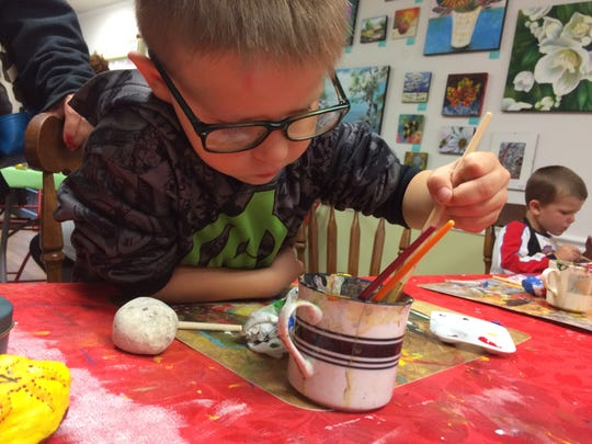 """Benjamin Krause, 5, uses a variety of colors and his own """"swirl"""" method of painting rocks for the Fondy Rocks!!! project that has been spreading throughout the community. Wednesday, Sept. 7, 2017."""
