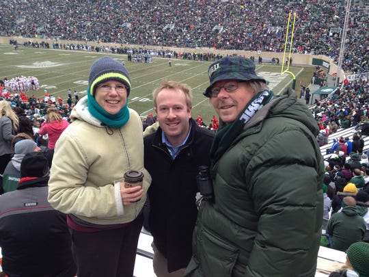 Lansing State Journal columnist Graham Couch, center, visits his mother Susan Henderson, left, and father Chris Couch, during an MSU football game late in the 2014 season. Chris, who had those seats for 22 seasons, died unexpectedly in August.