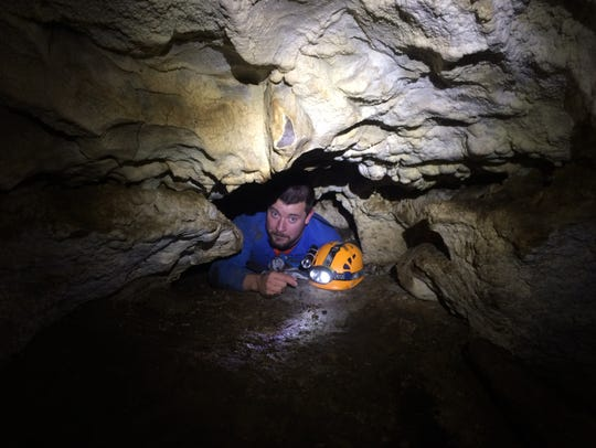 Zach Angstead crawls through a narrow passage in the