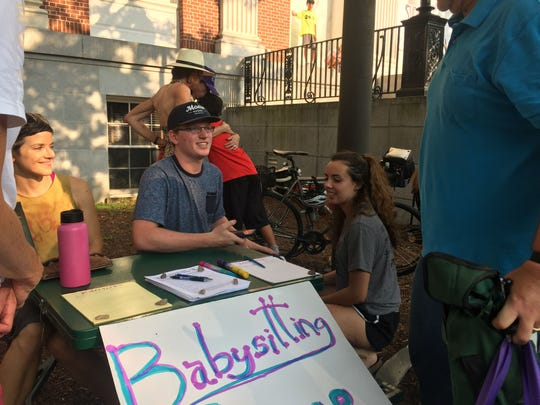 Vaughn Martin, center, a junior at Burlington High School speaks to a community member in City Hall Park on Sunday, Sept. 17, 2017, about a babysitting co-op formed by a group of high-schoolers to provide child care for younger students during the teacher strike.