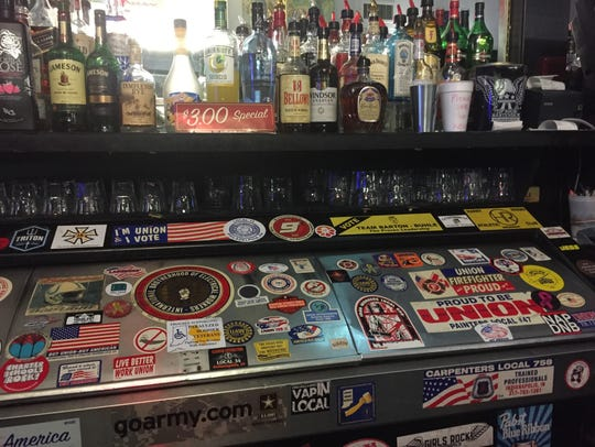 Various union stickers adorn the beer cooler behind