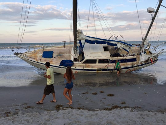 Beach-goers examine the grounded sailboat at Spessard