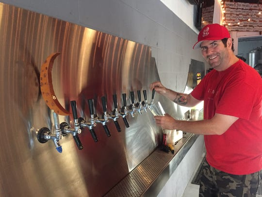 Lunacy co-founder Ed Gledhill pours a beer from a long row of taps at the brewery's new tasting room in Haddon Heights. The brewery hosts Sunday morning yoga.