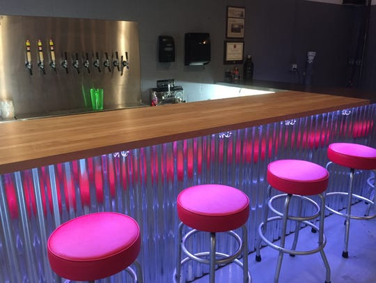 A long line of red bar stools offer seating close to