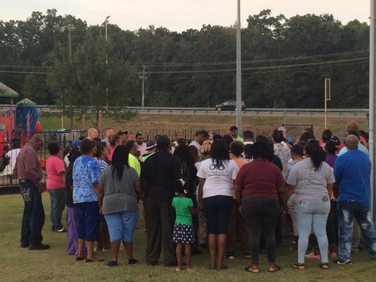 About 100 people gather around the family of James