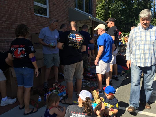 Firefighter families unload and sort boxes of donated food outside Lutheran Community Services in Wilmington.