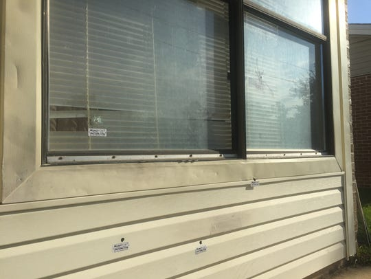 Five bullet holes remain in the front window and siding