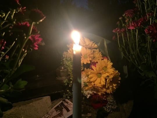 A candle and flowers are placed at Fort Ethan Allen