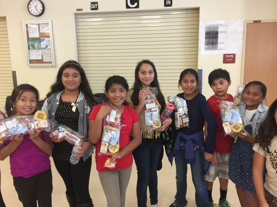 Tice Elementary School students display their food from Blessings in a Backpack SWFL.