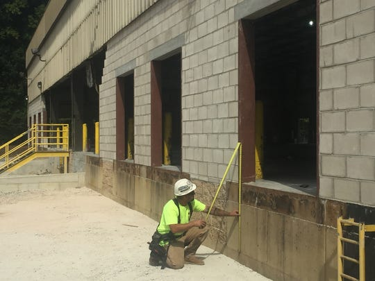 Carpenter foreman Jason Robert Fister of Atco takes measurernents in modifying loading docks  for a Burlington Township  distribution center for Bimbo Bakeries USA, largest baking company  in the U.S.