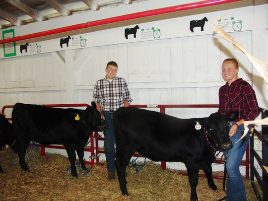 Ryan and Michaela Greten pose with their beef feeder heifers, Bella and Annie, before taking to the show ring in Hunter Arena.