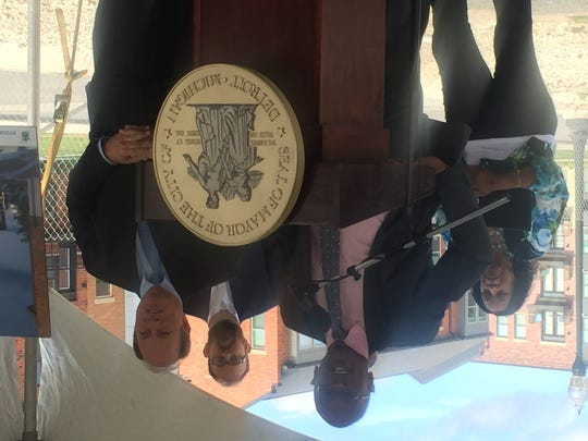 City planner Maurice Cox  (center) and Mayor Mike Duggan unveil plans for the renovation of the Stone Soap building.