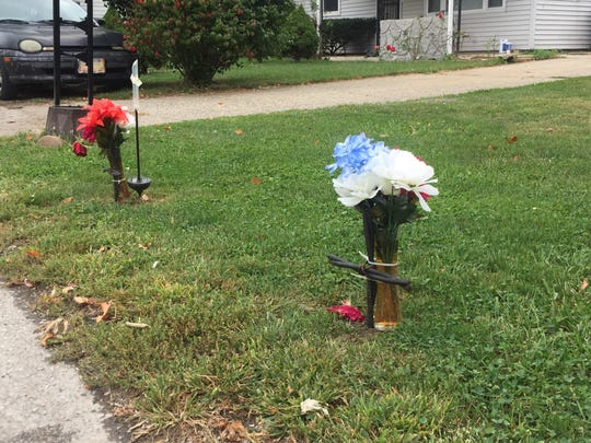 Two memorials in Cody Scott's front yard honor the memories of Catalina Lujano-Campuzano, 67, and her adult son, Gustavo Sanchez-Campuzan, 38. The two were gunned down  in front of these memorials Aug. 10 in the 800 block of Eastwich Drive. Nearly two months later, murder charges have not been filed against suspect Franco Navarrete, who is jailed on unrelated charges. That might change in the next week.