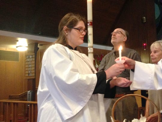 Nicole Benson (left) participates in a candle lighting ceremony at St. Paul's Episcopal Church in Ventura for the 58 victims who were killed in the Las Vegas shooting on Oct. 1. One candle was lit for each name read, followed by one ring of the church bell. Also pictured, from left, are Peter Bowers and Kay Armstrong.