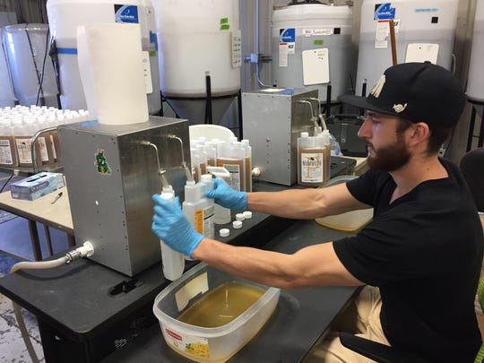Colin Harris of Growcentia bottles the plant-growth enhancer Mammoth P at the company's Fort Collins production facility.
