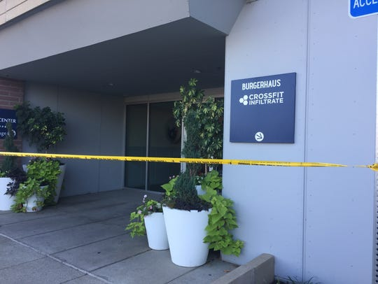 Crime scene tape blocks the front entrance to the fitness
