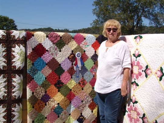 Ellen Lauvray poses by some of the quilts that she's