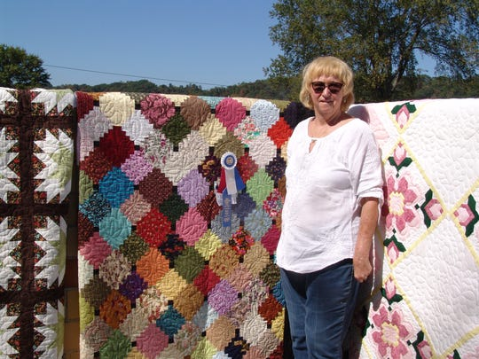 Ellen Lauvray poses by some of the quilts that she's made.