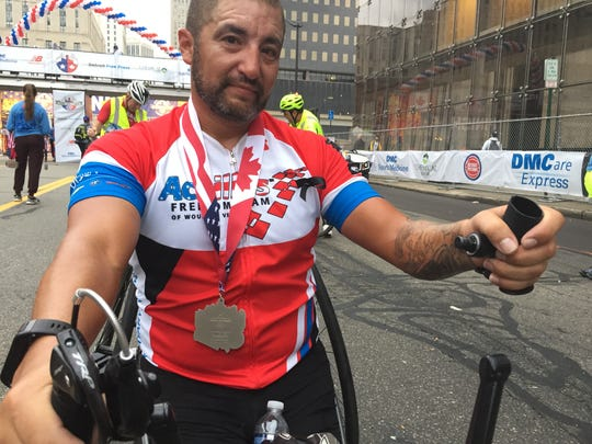 "Disabilities Div. winner Omar Duran of Clearwater, Fla., holds a handgrip that spun itself off his handcycle's crank mechanism in the last mile of Sunday's Detroit marathon -- but which didn't keep him from winning because ""I just pushed with what was left."""