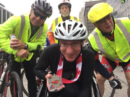 "Andrew Barnhart, 61, of Reading, Mich., celebrates being the only marathon finisher in a racing wheelchair -- despite having two flat tires. "" I never would've made it"" without his three bicycle escorts, Barnhart said."