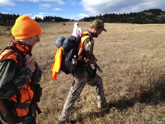 In this 2013 file photo, hunters Mary and Bob Ellenbecker of Missoula haul elk quarters after a member of their hunting party found success during the second week of hunting season. A report says 1.5 million acres of federal lands in Montana is landlocked.