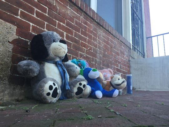 A collection of stuffed animals and candles was set up Tuesday morning outside the apartment where two boys were found dead the day before.