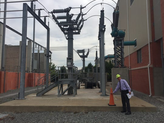 PSE&G's John Latka shows how high the storm surge from Sandy got at the substation in North Bergen along the Hudson River. Key equipment that had rested on the concrete pad has since been elevated far above that level to make the system more resilient in future storms.