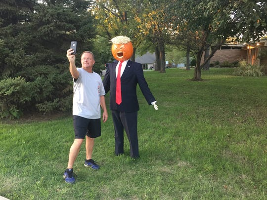 A man stops Oct. 18 to take a selfie with a Trump pumpkin standing by Main Street in Carmel.