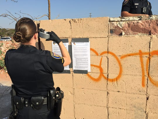An Oxnard police officers tapes up a notice at the former Halaco Engineering site telling homeless people to leave by Dec. 5.